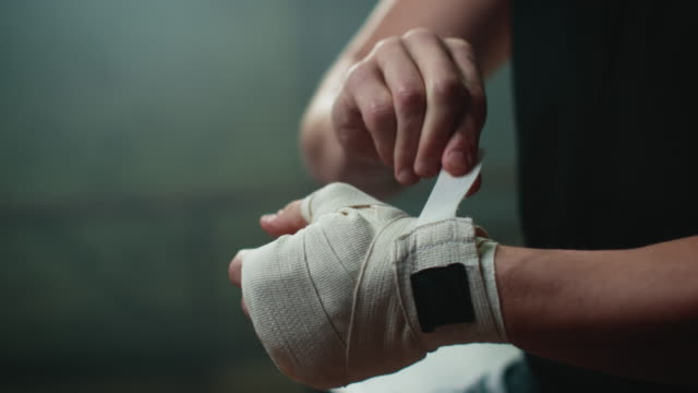 Boxer wrapping bandages around his hand A muscular boxer sitting in an old gym. He prepares himself for the sports training. He wraps bandages around his hand to protect his fingers. He is very focussed. There is some haze in the air. glove stock videos & royalty-free footage