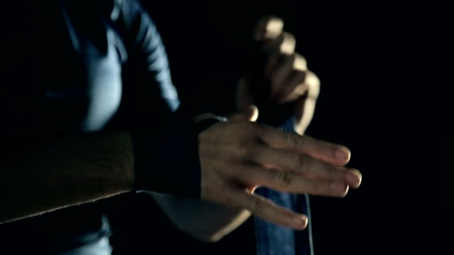 Boxer wraps his hands with Blue hand wrap before the fight training. video