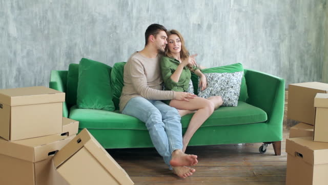 Boxes For Moving and the Happy Couple is Sitting Hugging on the Couch