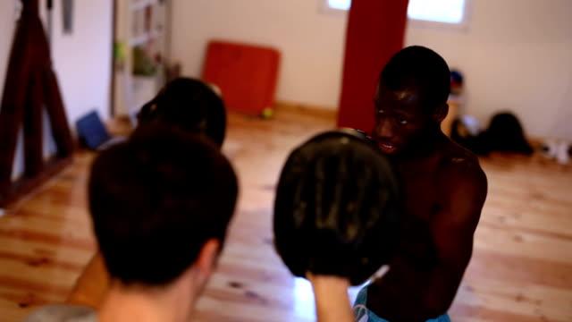 vídeos de stock e filmes b-roll de boxing class in dojo - boxe tailandês