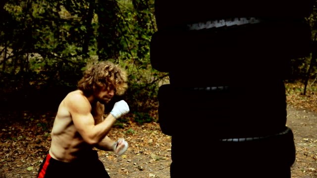 Boxing homemade pear, made from car tires. Fighter fulfills kick. video