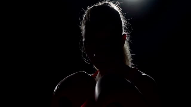 Boxing in the shadow. Struggling with weaknesses.Brunette punching her fists together video