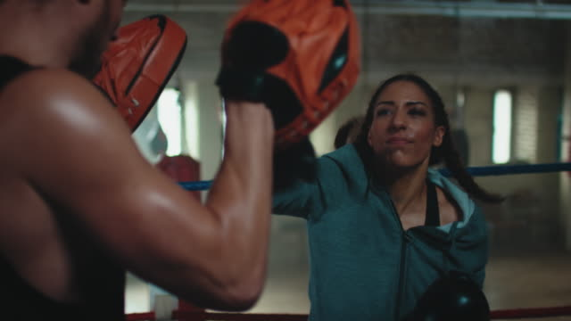 boxing trainer teaches woman - irriducibilità video stock e b–roll