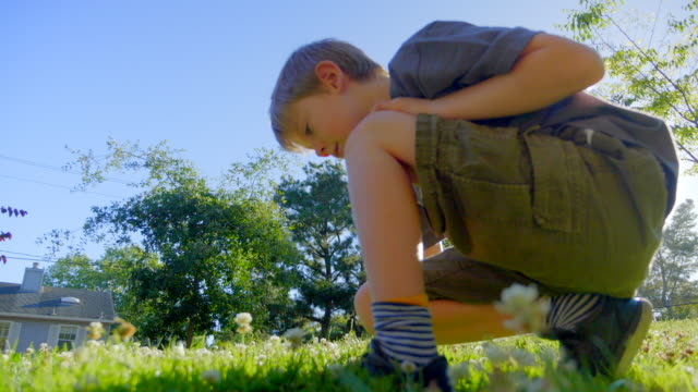 Boy 7 years old is sitting on the green grass in the park and enjoys the beautiful nature.