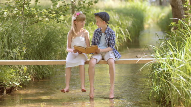 SLO MO A boy and a girl sitting on a footbridge and reading video