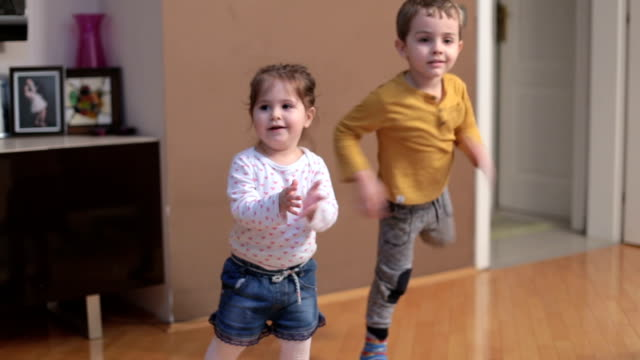 Boy and baby girl dancing and clapping in livingroom Girl is 23 months old, boy is 3 and a half years old. They are friends, but in this case they can be brother and little sister. There is music playing so they are jumping, dancing, and the little girl is mostly trying to imitate older boy elementary age stock videos & royalty-free footage