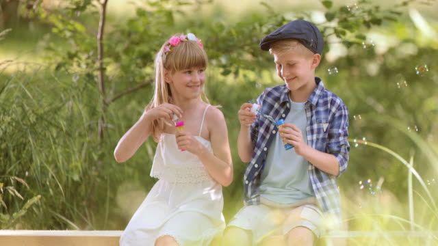 SLO MO Boy and girl blowing bubbles in nature video