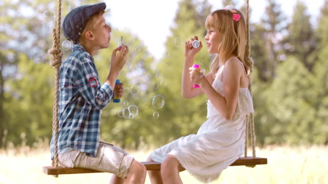 SLO MO Boy and girl blowing bubbles on a swing video