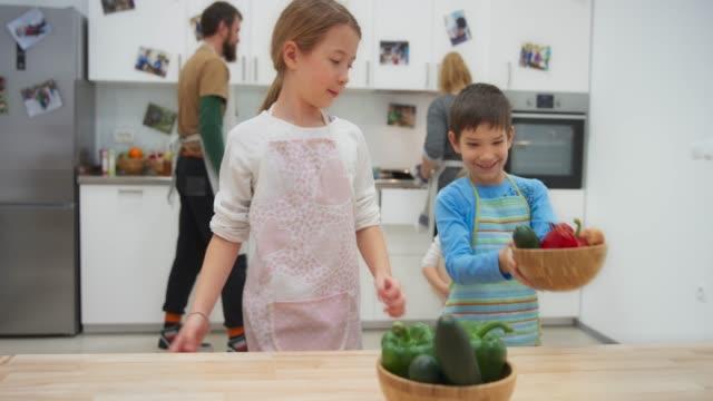 ds ragazzo e ragazza portando ciotole piene di verdure in tavola - 8 9 anni video stock e b–roll