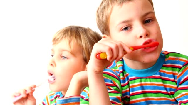 Boy and girl brush teeth, look against each other video
