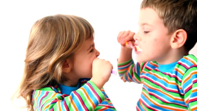 Boy and girl brush teeth looking against each other video