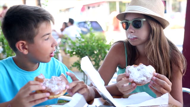 Boy and girl eating donuts in a bakery video