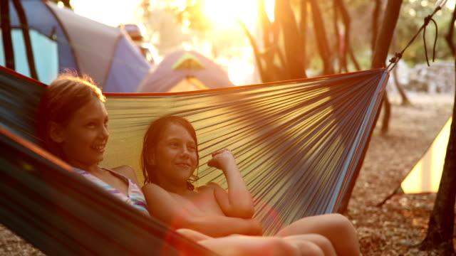 jungen und mädchen in hängematte auf camping genießen - ferienlager stock-videos und b-roll-filmmaterial