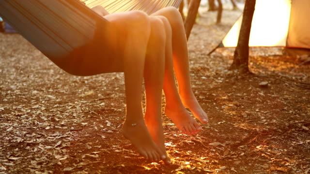 boy and girl enjoying in hammock on camping - amaca video stock e b–roll