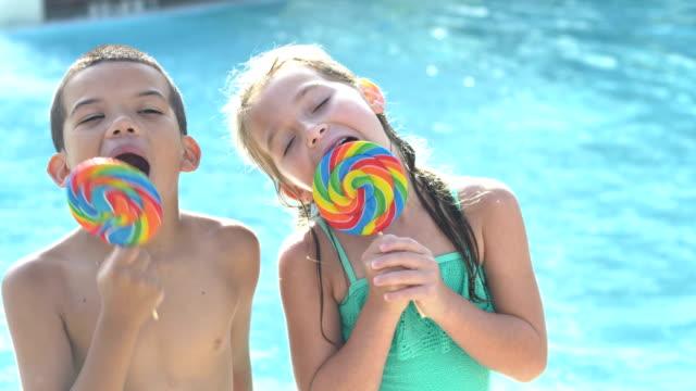 boy and girl enjoying lollipops at swimming pool - fare la lingua video stock e b–roll