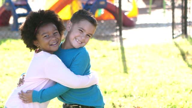 boy and girl, friends on the playground - serdeczny filmów i materiałów b-roll