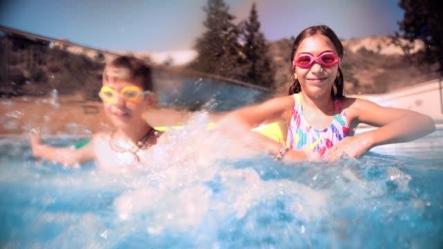 Garoto e garota se divertindo salpicos de água na piscina - vídeo