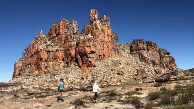 Boy and girl Hiking past a spectacular rock formation