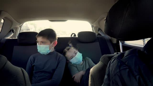 Pojke och flicka i skyddande ansiktsmasker i baksätet av att flytta bil i stadstrafik. Brother nad syster fith far under coronavirus epidemi och självisolering video