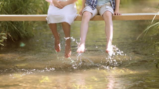 SLO MO – Jungen und Mädchen auf der Fußgängerbrücke planschen Wasser – Video