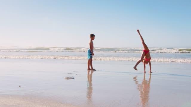 vídeos de stock, filmes e b-roll de menino e menina nas férias de verão jogando na praia juntos - férias na praia