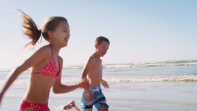 vídeos de stock, filmes e b-roll de garoto e garota verão férias correndo ao longo da praia e acenando juntos - férias na praia
