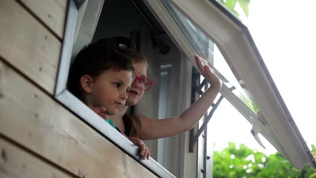vídeos de stock e filmes b-roll de boy and girl open the window and look at street - open window