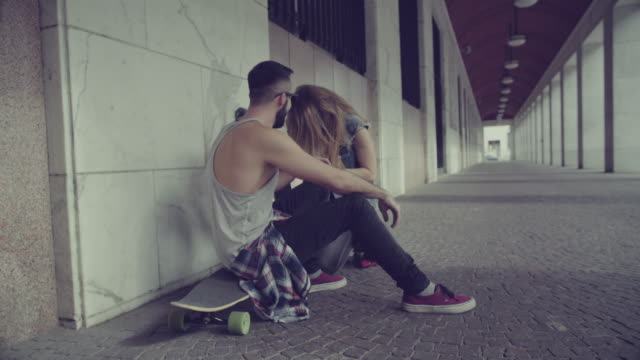 Boy and girl skaters relaxing in urban setting video