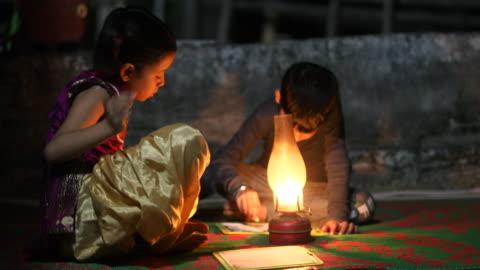 vídeos de stock e filmes b-roll de boy and girl studying in oil lamp - aldeia