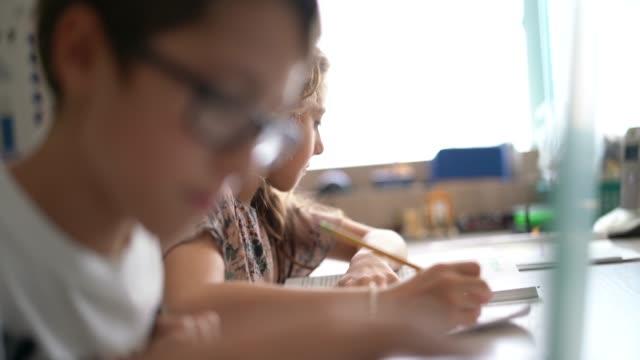 chłopiec i dziewczyna uczą się razem w domu - praca domowa filmów i materiałów b-roll