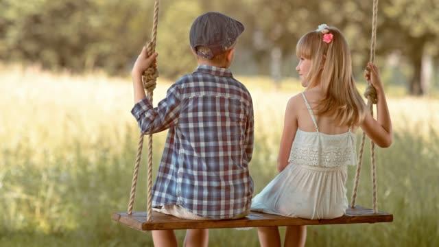 slo mo ragazzo e ragazza fiore sotto un albero - pantaloncini video stock e b–roll