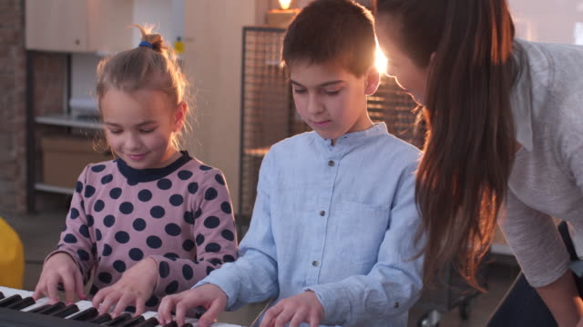 Boy and girl teaching to play synthesizer