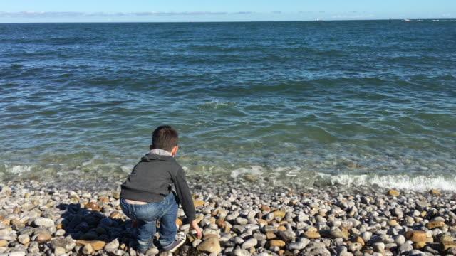 jungen und mädchen werfen kieselsteine in einem ruhigen meer entspannen - stein baumaterial stock-videos und b-roll-filmmaterial