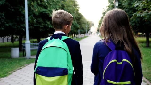 vídeos de stock e filmes b-roll de boy and girl walking with a school bags - passagem de ano