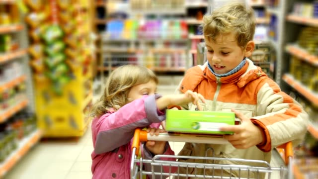Boy and girl with shopping trolley looks at goods box video