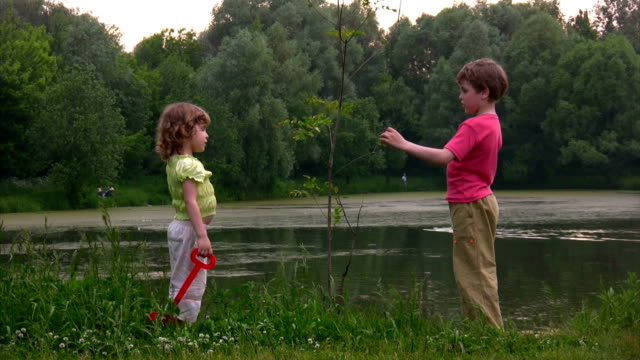 Boy and girl with shovel near plant video