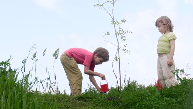 Boy and girl with shovel talks about plant video
