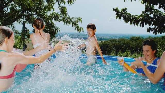 vídeos de stock e filmes b-roll de ms boy and girls playing,splashing in swimming pool - brinquedos na piscina