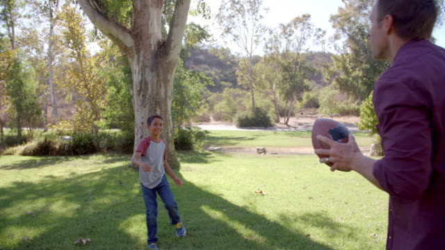 vidéos et rushes de garçon et son papa jouant avec le football américain dans un stationnement - lancer
