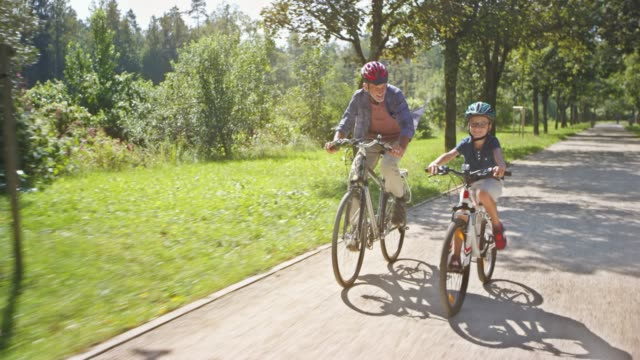 ts-boy und seinem opa reiten fahrräder im sonnigen park - aktiver senior stock-videos und b-roll-filmmaterial