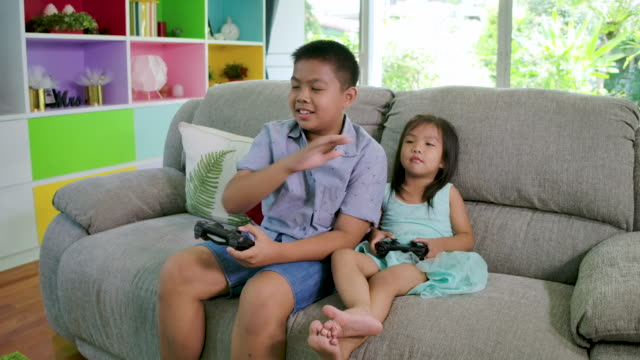 Boy and his sister playing video game fight at home.