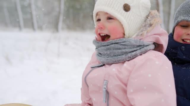 pojke och liten flicka i rosa jumpsuit spann på snöig vinterdag. föräldrar drar släde med son och dotter på snöfall. leende barn släde utomhus. människor slädtur, njuta av jullov - snow kids bildbanksvideor och videomaterial från bakom kulisserna
