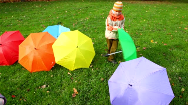 Boy and little girl puts umbrellas in park video