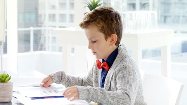 Boy as business executive verifying document 4k video