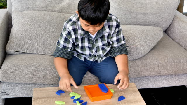 Boy asian children solving jigsaw puzzle on desk in the room.