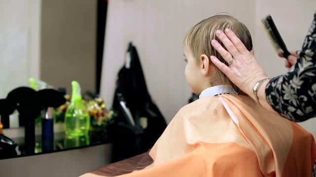 ragazzo in un salone di parrucchiere. - bassino video stock e b–roll