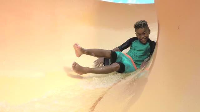 boy at water park sliding down waterslide - slitta video stock e b–roll