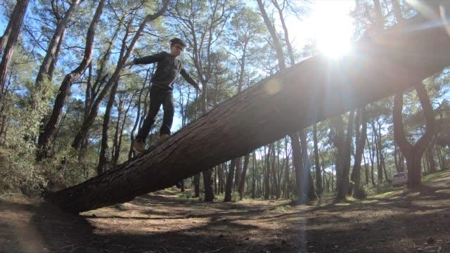 Boy balancing on fallen tree to cross stream in forest