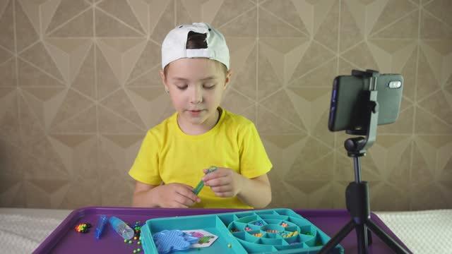 vidéos et rushes de garçon blogueur raconte émotionnellement quelque chose à l'appareil photo d'un smartphone - interview