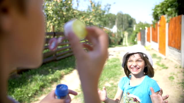 boy blowing bubbles, a girl trying to catch soap bubbles, slow motion video